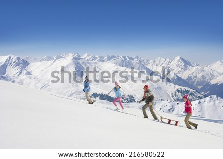 Family pulling sled uphill with mountains in background - stock photo