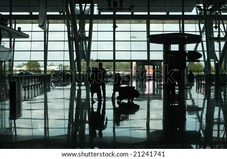 family pushing a trolley in the airport - stock photo