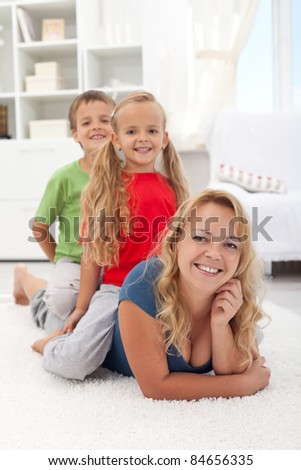Family quality time - woman with kids laying on the floor at home - stock photo
