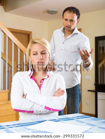 Family quarrel. Sad husband and woman during quarrel  in living room at home - stock photo