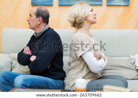 Family quarrel. Upset mature female against elderly man at home. Focus on woman - stock photo