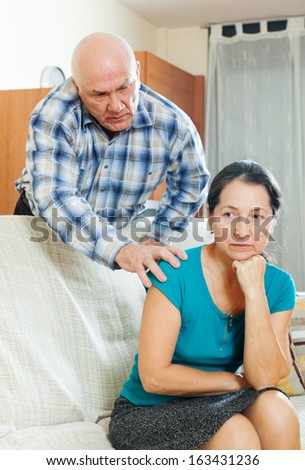 Family quarrel. Upset mature woman with husband at home - stock photo