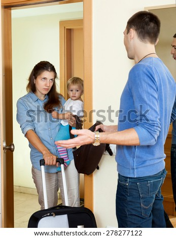 Family quarrel. Woman with baby girl leaving from her husband - stock photo