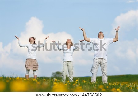 family raising arms high and carrying something on their hands - stock photo