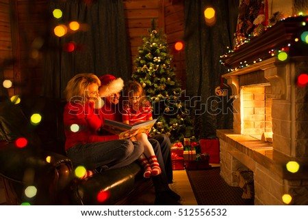 Family read book sitting on sofa in front of fireplace in Christmas decorated house interior