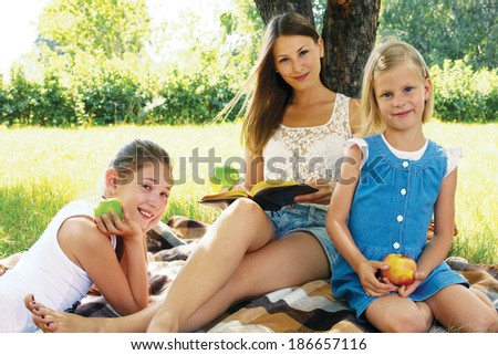 Family reading a book on a picnic - stock photo
