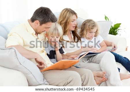 Family reading a book on their sofa at home - stock photo