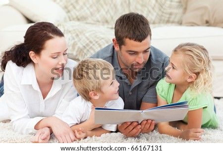 Family reading a book together lying on the floor at home - stock photo