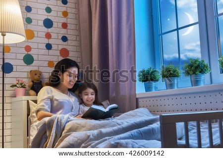 Family reading bedtime. Pretty young mother reading a book to her daughter. - stock photo