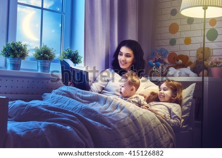 Family reading bedtime. Pretty young mother reading a book to her daughters. - stock photo