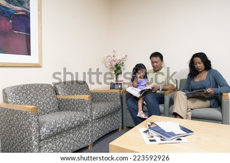 Family reading magazines in waiting room - stock photo