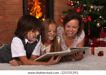 Family reading stories at Christmas time - laying by the fire - stock photo