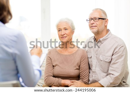 family, relations, age and people concept - happy senior couple and psychologist or social worker at home - stock photo