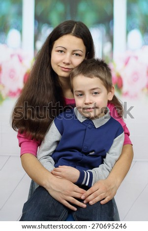 Family relations concept - little brother and teenage sister portrait in interior - stock photo