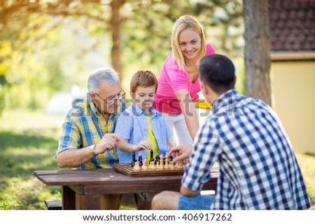 family relax time playing chess in nature - stock photo