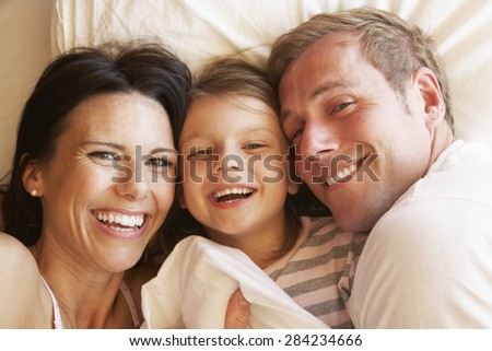 Family Relaxing In Bed - stock photo