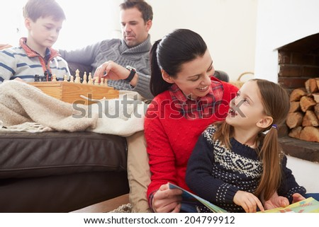 Family Relaxing Indoors Playing Chess And Reading Book - stock photo