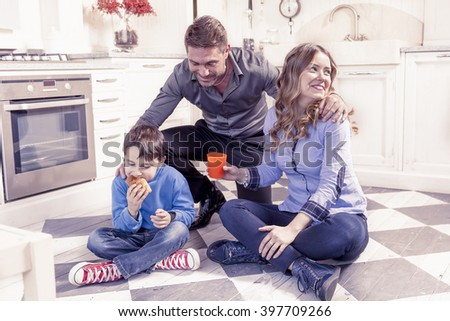 family relaxing on floor in the kitchen - stock photo