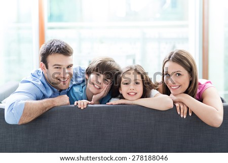 Family relaxing on sofa - stock photo