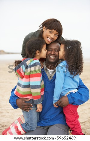 Family Relaxing On Winter Beach Break - stock photo