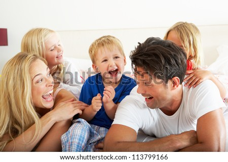 Family Relaxing Together In Bed - stock photo