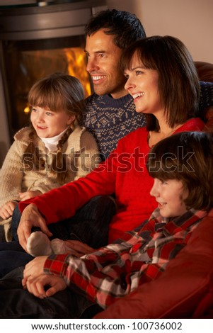 Family Relaxing Watching TV By Cosy Log Fire - stock photo