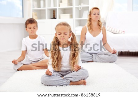 Family relaxing with yoga - balanced life concept - stock photo