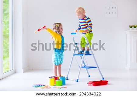Family remodeling house. Home remodel and renovation. Kids painting walls with colorful brush and roller. Children paint wall. Choice of bright color on sample palette for child nursery or kid room. - stock photo