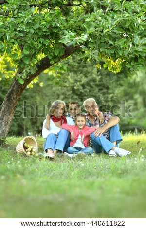 Family resting in park with apples - stock photo