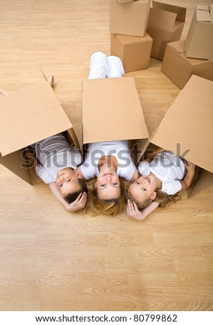 Family resting on the floor in their new home while unpacking - stock photo