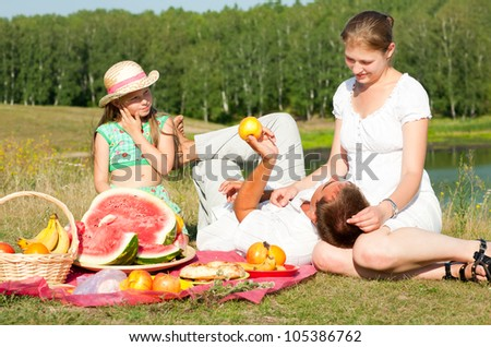 family resting on the lake - stock photo