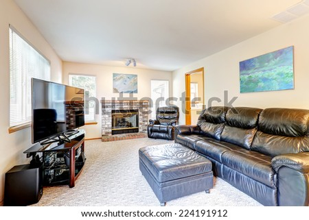 Family room interior design. Rich black leather furniture set, fireplace and tv. - stock photo