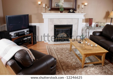 Family room interior with flat screen tv, leather furniture and a beautiful marble fireplace.