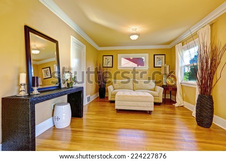Family room with cozy sitting area. Comfortable love seat and ottoman. Room decorated with wicker vases and dry bushes. Wicker table with candles and mirror - stock photo