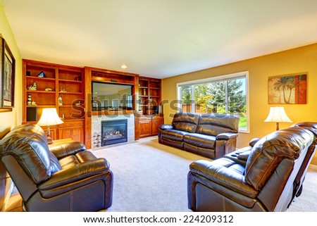 Family room with rich leather furniture set, cozy fireplace and tv. Room has built-in storage combination - stock photo