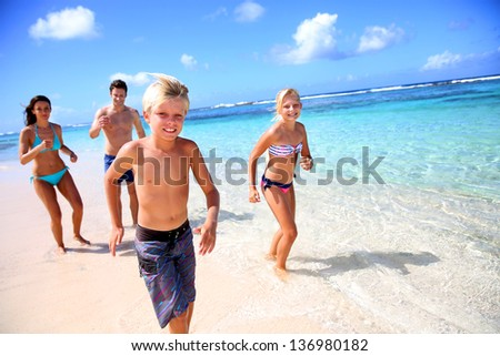 Family running on a paradisaical beach - stock photo