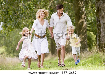 Family running on path holding hands smiling - stock photo