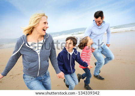 Family running on the beach - stock photo
