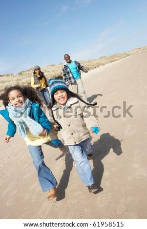 Family Running On Winter Beach - stock photo