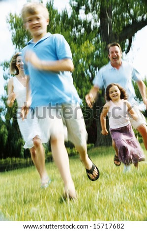 Family running outdoors smiling - stock photo