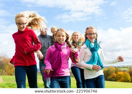 Family running through park in fall or autumn - stock photo