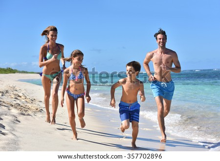 Family runnning on a sandy beach in Caribbean island - stock photo