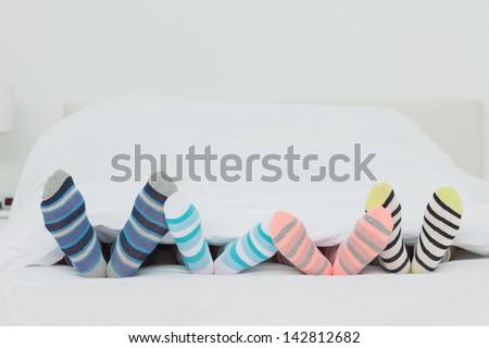 Family's feet in stripey socks at home in bed - stock photo