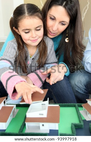 Family sat with model housing - stock photo