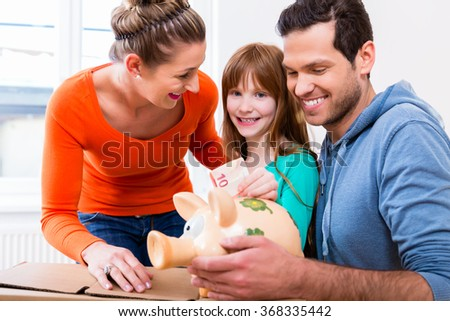 Family saving money by moving house putting bank note in piggybank - stock photo