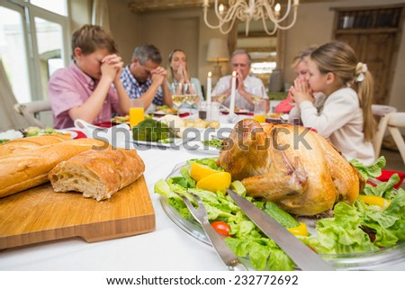 Family saying grace before christmas dinner together at home in the living room - stock photo