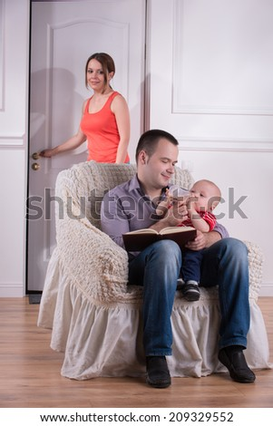 Family scene, father and son sitting in cozy armchair and feeding baby with bottle, mother entering the room, studio shot - stock photo