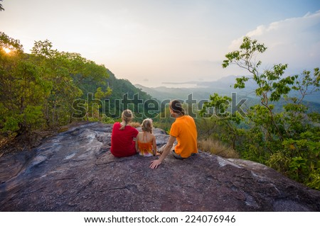 Family seat near cliff on the top of tropical island mountain on sunset