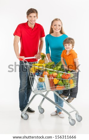 Family shopping. Cheerful family standing near shopping cart and smiling while isolated on white - stock photo