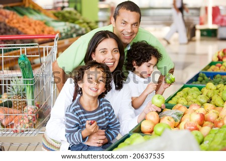 Family shopping in supermarket for some fruit and vegetables - stock photo